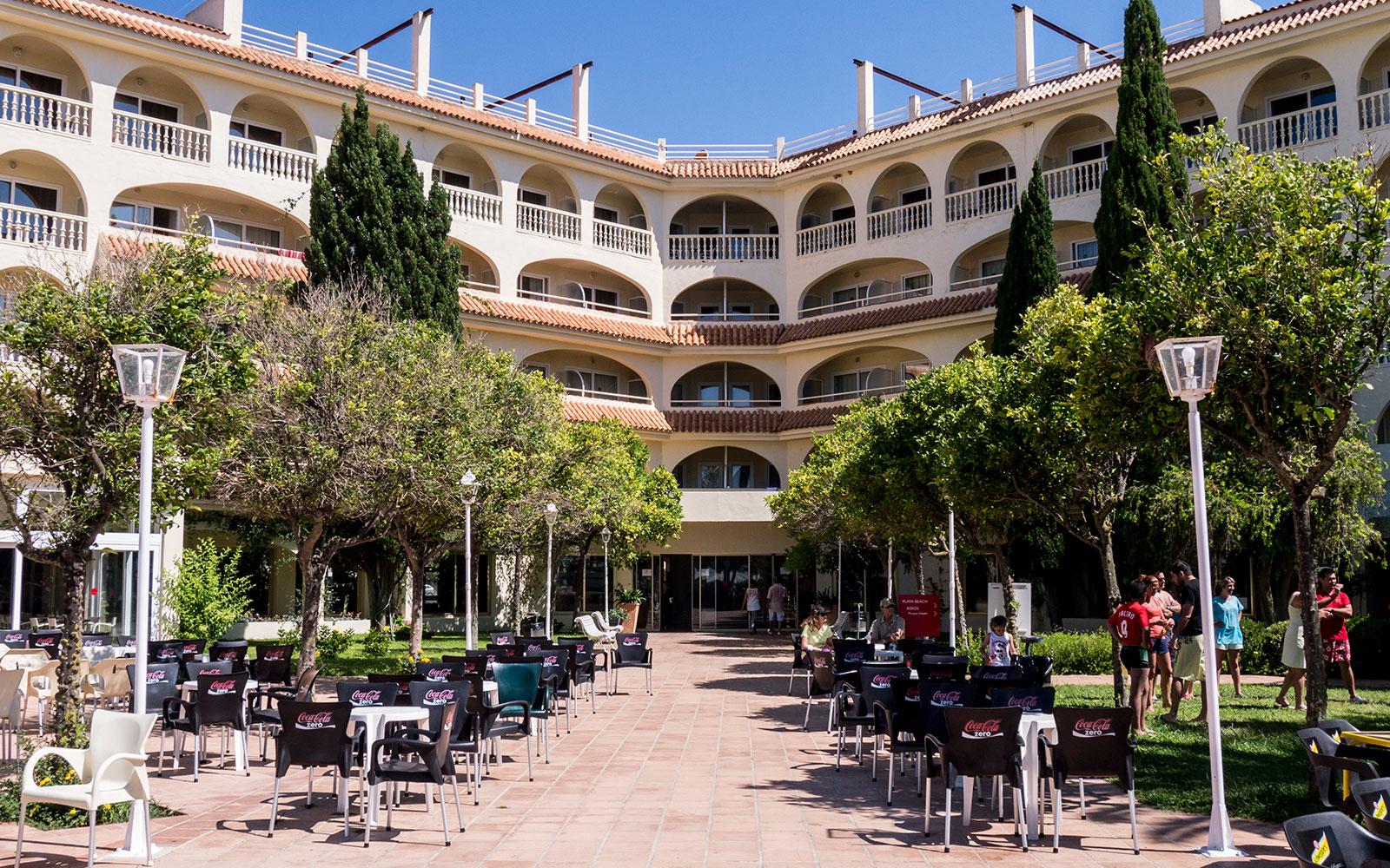 Fachada del hotel vista desde patio ajardinado con mesas