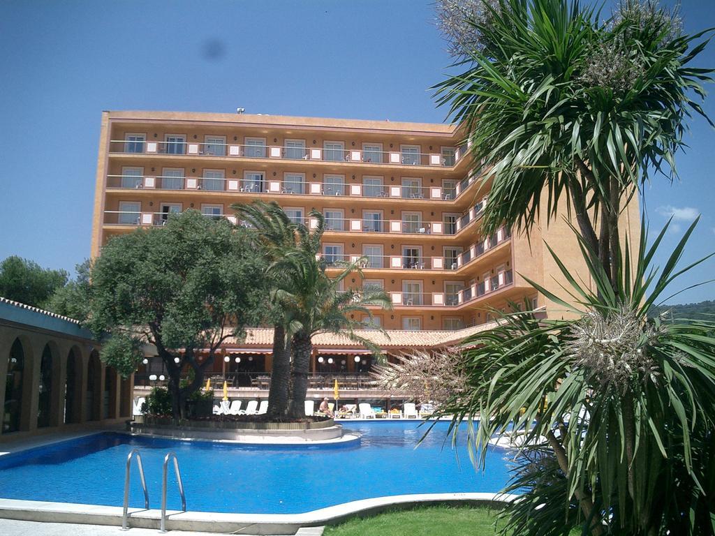 Fachada del hotel con la piscina y palmeras