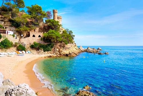 Cala de la Costa Brava con castillo y árboles la fondo