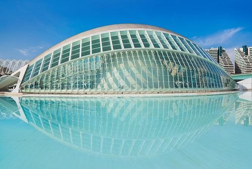 Edificio de metal y cristal con forma de ojo junto a un lago artificial