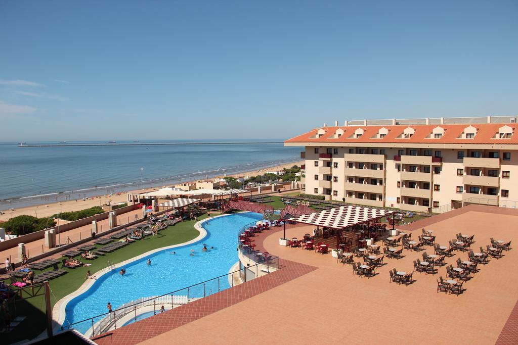Vista exterior con la piscina y playa al fondo