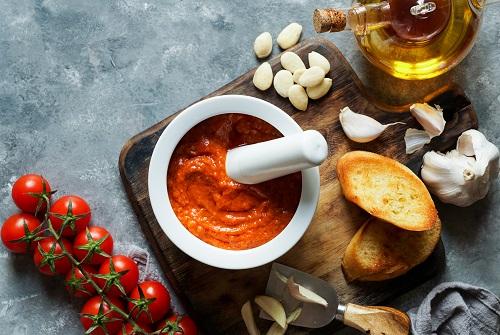 Mordero de cocina con aceite, pan, ajo y tomate