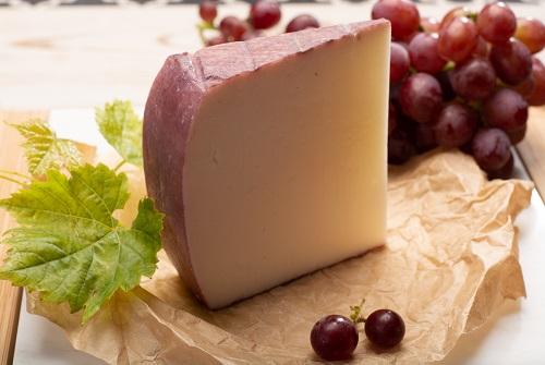 Cuña de queso con un racimo de uvas